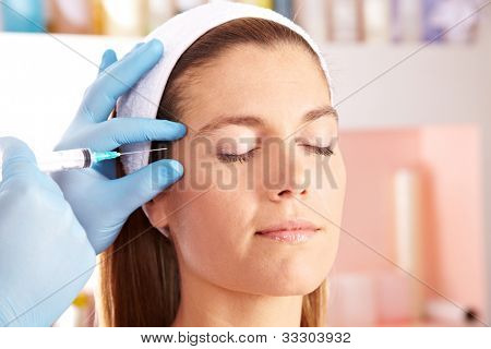 Woman in beauty clinic getting injection to remove eye wrinkles
