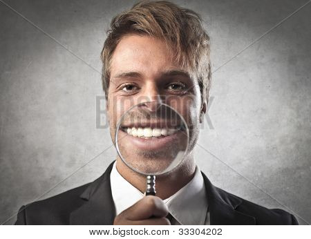 Young businessman zooming on his smile with a magnifying glass