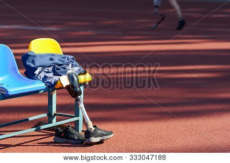Sneakers, Wear And Prosthetic Leg Laying On A Seat While Their Owner Run Near By