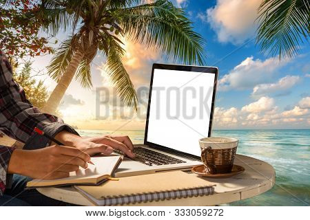 Businessman Hand Write Make A Note Of Notebook Working With Laptop Computer, Coffee On Table At Land