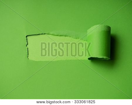 Small Paper Hole With Torn Sides Over Green Background For Your Text, Print Or Promotional Content.