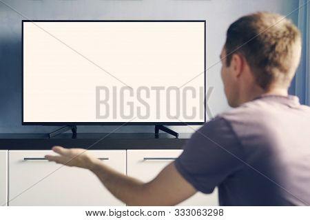 A Young Guy Emotionally Watching Tv And Waving His Hands In Discontent. Blank White Screen For Desig