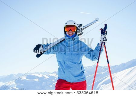 Photo of athlete man in helmet and mask with skis on his shoulder