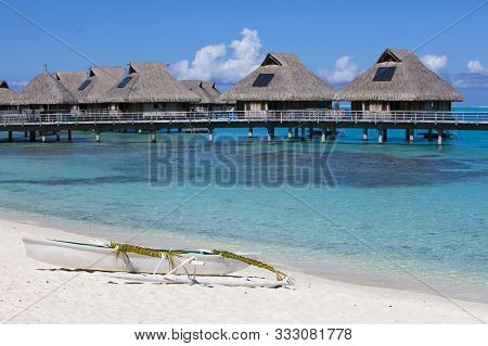 Focus On A Beautiful White Traditional Polynesian Boat With Oars Braided By Reeds On The Sandy Shore
