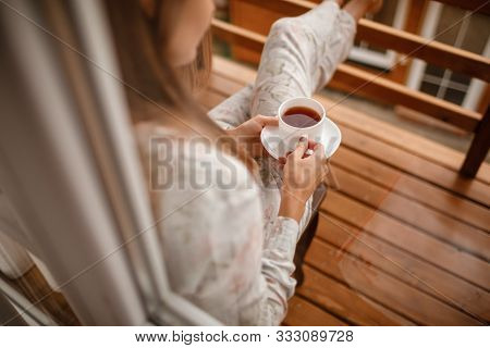 Young Woman In Stylish Nightwear Enjoy Drinking Coffee Or Tea Outdoor On Balcony In The Morning And