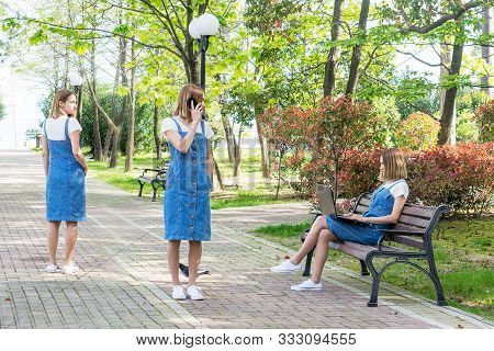 The Concept Of Genetic Cloning. Three Young Girls In The Park Look Alike