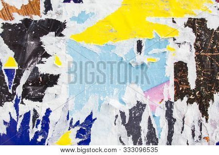 Dirty Ripped And Peeling Paper Posters On A Wall. Grungy Street Billboard With Old Motley Placards T