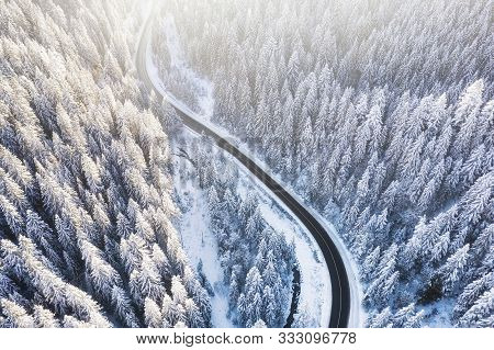 Aerial View On The Road And Forest At The Winter Time. Natural Winter Landscape From Air. Forest Und