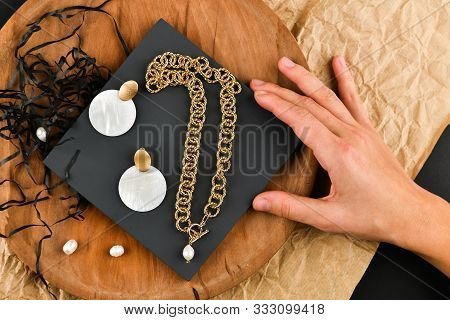 Gold Earrings With A Necklace. Close-up. Laid Out On A Wooden Stand. View From Above. The Concept Of