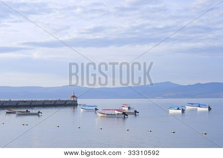 Skiffs and fishing boats anchored in harbor off Lake Chapala pier in Chapala Mexico poster