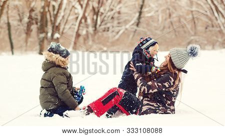Lovely Kids And Mother Having Fun Together In Snow At Park. Winter Outdoors Game. Winter Holidays, V