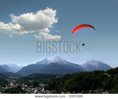 Very beautiful landscape in the german Alps with the mountains Watzmann and Hochkalter a Para glider and the village of Berchtesgaden poster