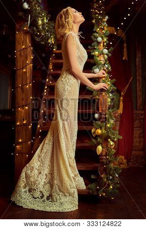 Christmas and New Year celebration. Charming young woman in luxurious evening dress and with beautiful evening makeup and hairstyle meets Christmas in a luxurious interior. X-mas fashion concept.