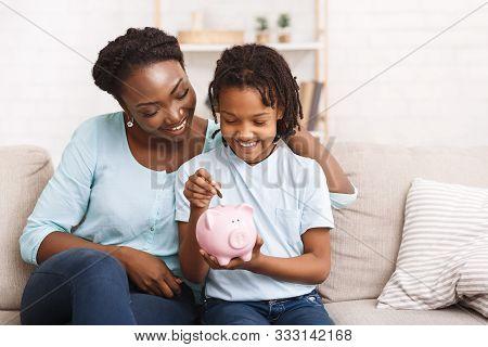 Children And Economy. Little African American Girl Putting Coin In Piggybank, Saving Money.