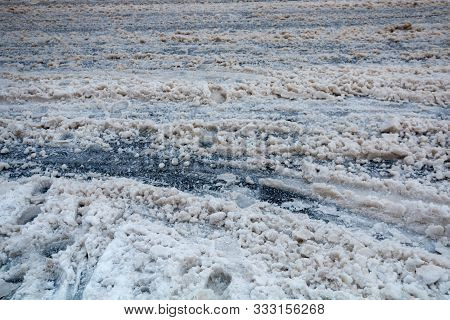City Street With Dirty Slush, Mush Of Snow. Drive Carefully