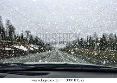 Vehicle Safety In Winter. Car Driving In Dangerous Winter Weather With Poor Visibility During Snowfa