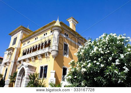 Beautiful View Of Yellow House And White Flowers  On A Sunny Day. Traditional Architecture. Cascais.