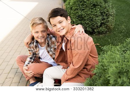 Two Cheerful Brothers Smiling While Sitting On Pavement And Looking At Camera
