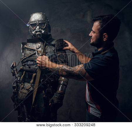 One Colleague Is Fixing Costume Of Futuristic Warrior On Another Man At Dark Photo Studio.