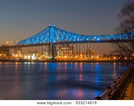 Long Exposure Shot Of Jacques Cartier Bridge Illumination In Montreal, Reflection In Water. Montreal