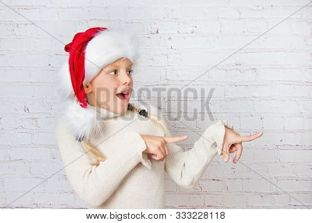 happy little santa Claus hat girl pointing at christmas