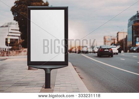 A Blank Vertical Street Poster Template On A Sidewalk In Evening Urban Settings; An Outdoor Billboar