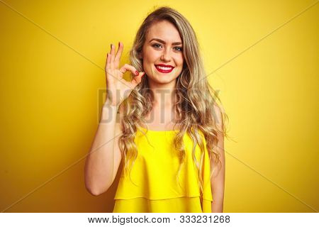 Young attactive woman wearing t-shirt standing over yellow isolated background smiling positive doing ok sign with hand and fingers. Successful expression.