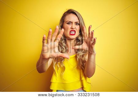 Young attactive woman wearing t-shirt standing over yellow isolated background afraid and terrified with fear expression stop gesture with hands, shouting in shock. Panic concept.