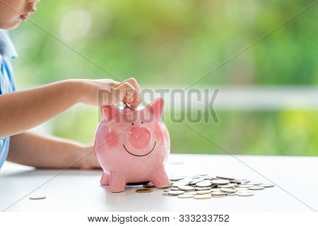 Little Boy Putting Coin Into Piggy Bank For Saving With Pile Of Coins On Table At Home.a Pink Piggy