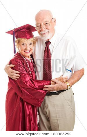 Senior woman graduating from college, standing with her proud, supporting husband.  Isolated on white.