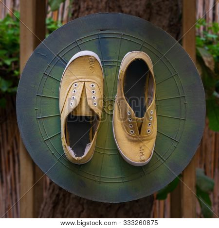 Shabby Ruined Yellow Shoes With Stitches Attached To Grunge Green Dartboard Game Board On Tree Trunk