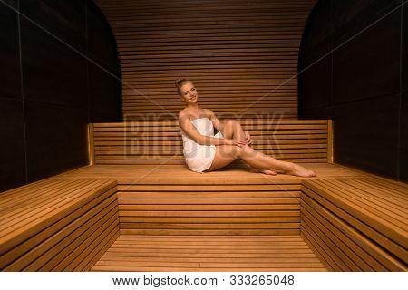 Woman doing a steam bath in a wooden sauna room