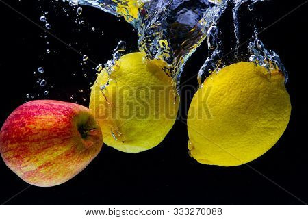 Ripe Yellow Lemons And Red Apple Fall Into The Water And Create Beautiful Water Swirls And Bubbles O