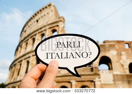 closeup of the hand of a caucasian man holding sign with the question parli italiano? do you speak Italian, written in Italian, in front of the Flavian Amphitheatre or Colosseum, in Rome, Italy