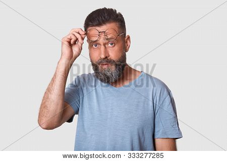 Close Up Portrait Of Good Looking Caucasian Bearded Guy Taking Off Glasses, Holding Frames Near Fore