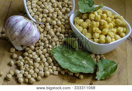 Dried Chickpeas And Boiled Chickpeas Arranged On A Kitchen Counter Top Along With Bay Leaves And Gar