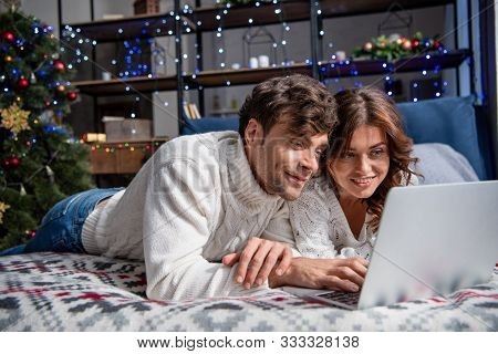 Smiling Boyfriend And Girlfriend In Sweaters Looking At Laptop At Christmastime