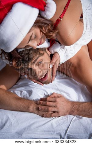 High Angle View Of Girlfriend In Santa Hat Hugging Boyfriend At Christmastime