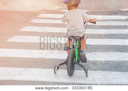 A Four-year-old Boy Rides A Bicycle On A Pedestrian Crossing, The Carriageway Alone Without Parents.