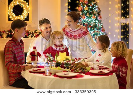 Family With Kids Having Christmas Dinner At Tree