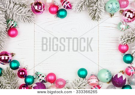 Christmas Frame With Pink, Purple And Teal Baubles And Tree Branches. Top View On A White Wood Backg