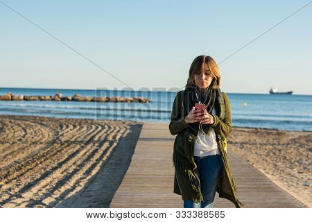Stock Photo Of A Young Woman While She Is Walking With A Smartphone In The Beach At Sunset. Lifestyl