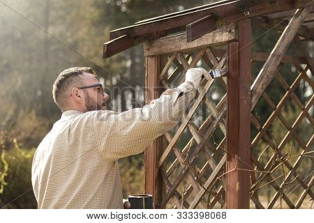 The Man In The Garden Paints Brown Wooden Boards Of The Garden Furniture. Renovation And Maintenance