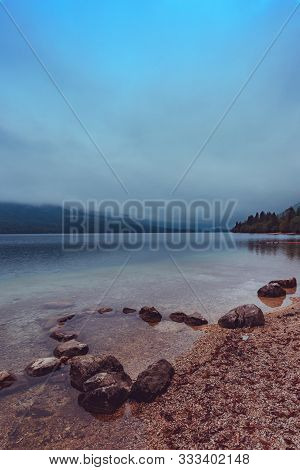 Crack Of Dawn On Lake Bohinj In Slovenia, Beautiful Tranquil Landscape With Autumnal Fog On The Lake