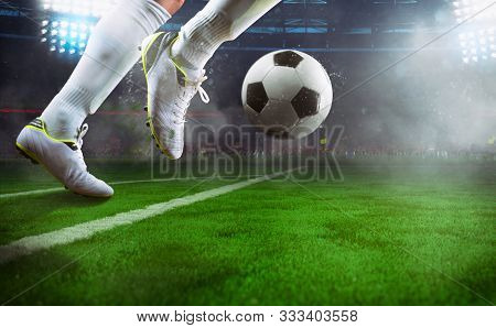 Football Scene At Night Match With Close Up Of A Soccer Player Running To Kick The Ball At The Stadi