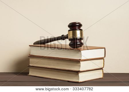 Law Concept. Wooden Judge Gavel And Law Books On Table In A Courtroom Or Enforcement Office.