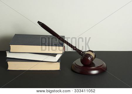 Law Concept . Books With Wooden Judges Gavel On Black Table In A Courtroom Or Enforcement Office.