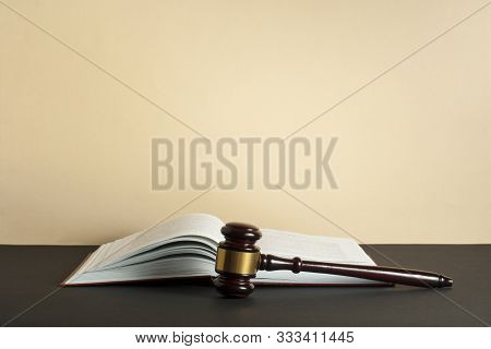 Law Concept - Open Book With Wooden Judge Gavel On Table In A Courtroom .