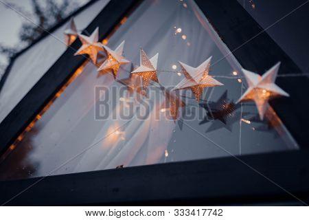 Garland Of Stars On The Evening Street Window. Christmas, Holidays, New Year, Travel, Eco Hotel.