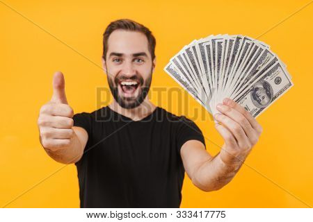 Image of unshaved man wearing basic black t-shirt smiling and holding money cash isolated over yellow background